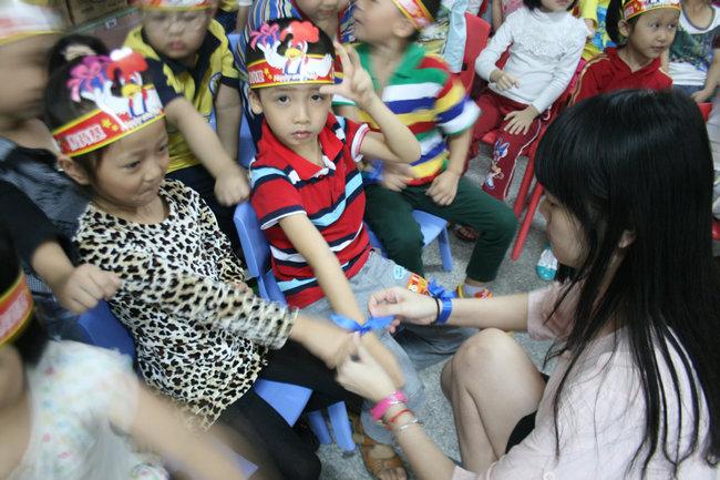 幼儿园老师给小朋友们系上蓝丝带